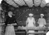 """I """"gamla bagarstugans"""" miljö där flitiga bagerskor håller på med att baka knäckebröd"""