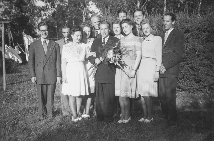 Tänkbar samling för att fira blomsterhyllade Henry Forsmark. Namn från vänster: Karl-Gustav Andersson, […], Elsie Viklund, Nancy Forsmark, Owe Sundström, Henry Forsmark, Anne-Marie Tollsten, Doris Eriksson, Karl-Gösta Sälgström, Mona Norström, […] Hjulström.